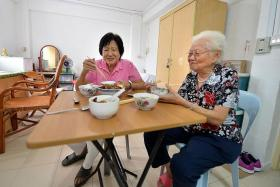 TOGETHER: (From left) Madam Hou Wah Cheng and Madam Lee Ah Sim, both 80, share a meal in their one-room rental flat at Pipit Road.