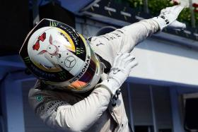 LIKE BOLT:Lewis Hamilton hamming it up for the camera after his win at yesterday's Hungarian GP.
