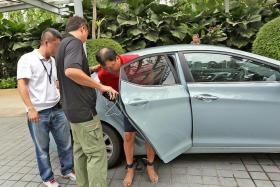 ACCUSED: Leslie Khoo Kwee Hock accompanied by plain-clothes police officers at Gardens by the Bay yesterday.