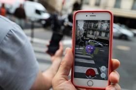 CATCH 'EM: This picture taken on Tuesday near the Louvre museum's pyramide in Paris shows the Pokemon Go app on a smartphone screen.