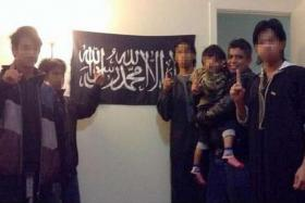 ARRESTED: Zulfikar Mohamad Shariff (carrying child) posing with a black flag that is commonly used by ISIS fighters.