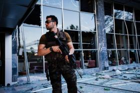 ON ALERT: An armed Turkish police officer standing guard in front of the damaged police headquarters after it was bombed during the failed coup attempt.