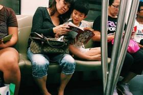RIDE & READ: A woman spotted reading to her child on the MRT.