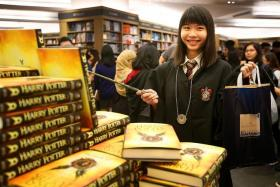 FIRST IN LINE: Ms Mavis Tan was the first one to pick up her book at the cashier when Kinokuniya opened at 7:01am.