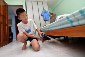 BETTER TOTNP PHOTOS: JEREMY LONG BE SAFE: Zhengda spraying insecticide in dark corners of his flat.