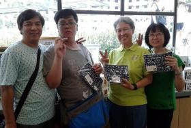 GOOD CAUSE: See Toh Sheng Jie (second from left) with his parents and Ms Ho Ching, who is holding the dinosaur pouch he designed.