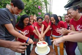 FUN: A cake-cutting session at the party (above), foreign workers and youth volunteers bonding through games, Mr Chauncey Mirchandani at the party.