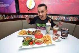 ATTACK! ONE FM 91.3 radio DJ Elliott Danker gets ready to try the food at DC Comics Super Heroes Cafe at The Shoppes at Marina Bay Sands.