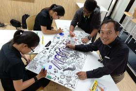TALENTED: (Above) Mr Liew doodling with his art class students.