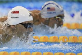 Joseph Schooling competes in the men's 100m butterfly heats, next to Michael Phelps.