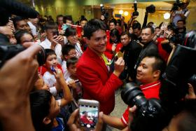 Singapore Olympic gold medallist swimmer Joseph Schooling shows his medal to fans during a homecoming ceremony at Singapore's Changi Airport