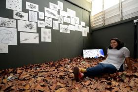 TALENTED: Ms Nur Aqilah Hassan with her work for an exhibition - While They Trim Trees, We Reshuffle Leaves - this year.