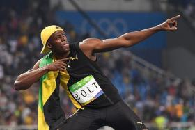 """BOLT STRIKES THRICE: Usain Bolt (right) posing in his """"lightning-bolt"""" pose after winning his third straight Olympics 100m race."""