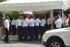 PAYING RESPECTS: (Above) Pallbearers carrying Mr S R Nathan's casket into his family home.