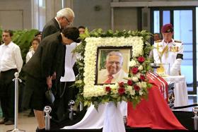 Preisdent Tony Tan Keng Yam and his wife Madam Mary Chee bow in front of Mr S R Nathan's casket at Parliament House.