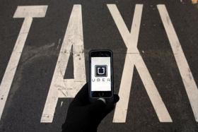 UBER ON HAND: The logo of car-sharing service app Uber displayed on a smartphone.
