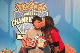 PASSION: Pokemon player Corey Elliot Yuen receiving a kiss from his mother, Madam Adelene Kong, after winning the Australian National title.
