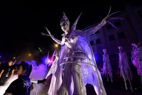 A WALK IN THE DARK: (Above) In Let's Celebrate, performers on stilts wove their way among the crowd.