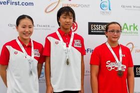 GOLDEN GIRL: Minami Takahashi (centre) wins the 12-year-old girls' 50m backstroke, ahead of Honoka Ishige (left) and Singapore's Elena Lee Lee Na Pedersen (right).