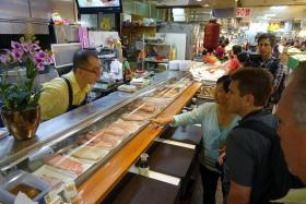 TAIWANESE TREATS: (Above) A sushi bar in the middle of the fresh seafood section at Shidong Market in Taipei.