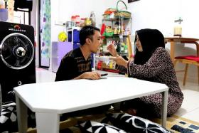 DEVOTED MUM: Madam Jurina Johari feeding her younger son Muhammad Shahirul Junadi at a table that as donated by a well-wisher.