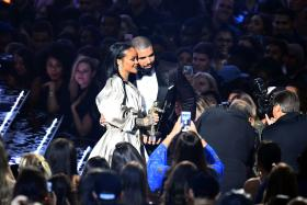 Drake escorts Rihanna after presenting her with The Video Vanguard Award during the 2016 MTV Video Music Awards at the Madison Square Garden in New York on August 28, 2016.
