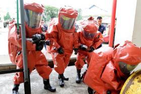 PRECAUTION: Hazmat specialists simulate plugging the gas leak.