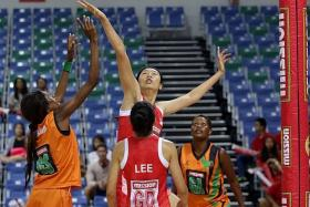 DEFENCE: Singapore's Chen Lili (below) attempts to block a shot from a Zambia player in their match in the Mission Foods Nations Cup.