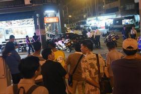 LATE-NIGHT DRAMA: Passers-by at the scene at Geylang Lorong 25A.
