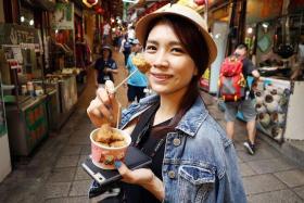 YUMMY: Sora Ma tucks into Jiufen's Deep-fried Mushrooms at Jiufen Old Road.