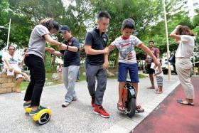 NEWBIE: Sparsh Agrawal (in blue shorts) being coached by Mr Tng Han Siang as he tries out the electric unicycle.