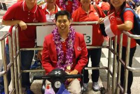 SUPPORT: Tan and fellow para-athlete Suhairi Suhani (standing, with garland) and their friends at the airport yesterday.
