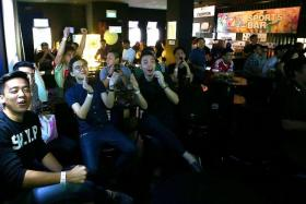 WELL DONE: Football fans cheering a Manchester United goal at the Tiger-TNP Sports Bar at Shanghai Dolly in Clarke Quay yesterday.