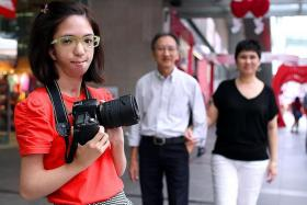 FOCUSED: Miss Isabelle Lim, who has Nager syndrome, dreams of being a photographer and has already staged an exhibition. Her parents are in the background. TNP PHOTO: LATASHNI GOBI NATHAN