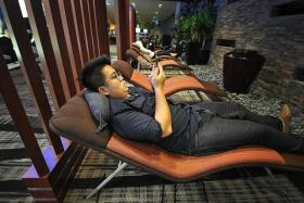 TNP reporter Ng Jun Sen tries to relax in Changi Airport's transit area.