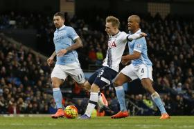 Tottenham midfielder Christian Eriksen shields the ball from Man City defender Vincent Kompany during their match at the Etihad Stadium in February 2016.