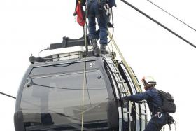 SAFE: An SCDF rescuer making his way to the top of the cable car. Another rescuer rappels down to the cable car and hooks the 'casualty' onto a harness. Then they lower 'him' down.