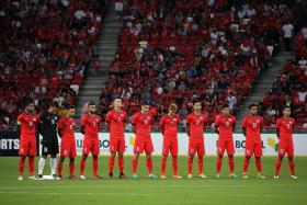 RESPECT: The Singapore players observing a minute of silence for ex-national winger S Anthonysamy before yesterday's Causeway Challenge at the National Stadium.