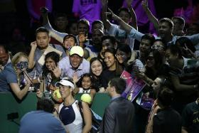 WEFIE: Garbine Muguruza (wearing visor) takes a picture with fans at last year's WTA Finals at the Indoor Stadium.