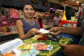 PHONE HOME: Ms Dipa Swaminathan buying phone cards to distribute to migrant workers during Deepavali.