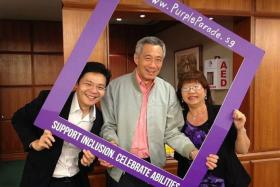 FILL THE FRAME: Prime Minister Lee Hsien Loong (centre) was 'ambushed' in 2013 by Ms Denise Phua, adviser to The Purple Parade committee and Mayor of Central Singapore District, to take a picture with a purple frame. On the PM's right is Mr Lawrence Wong, the Minister for National Development and Second Minister for Finance.