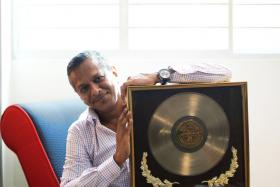 WINNER: Mr Derek Joseph with the award he received for placing first in the first Singapore Disco Dancing Competition.
