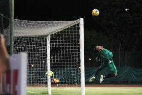SUNNY SPOT-ON: Lions goalkeeper Hassan Sunny making a save from Chan Vathanaka's free-kick.