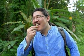 TINY SNACK: (Above) Mr Esmonde Luo biting into a ripe banana he found along the trail.