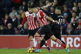 FRUSTRATED: Liverpool's (from right) Roberto Firmino is stopped in his tracks by Jose Fonte and Charlie Austin of Southampton.