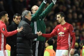 Henrikh Mkhitaryan shakes Jose Mourinho's hand as he is substituted in Manchester United's Europa League match against Feyenoord.