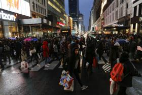 Shoppers cross the street carrying retail bags during Black Friday events