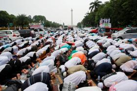 Indonesian Muslims attend Friday prayers during the rally.