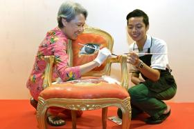 Rainbow Centre student Danial Isaac with Guest of Honour Ms Ho Ching, who is adding final touches to his chair 'Heart of Freedom'