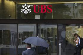 A pedestrian crosses the road outside the UBS Group AG's headquarters in Zurich, Switzerland